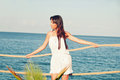 Girl with long hair in a short white dress on the pier travel Royalty Free Stock Image