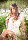 Girl with long hair sitting on meadow with white flowers sexy Royalty Free Stock Photo