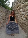 Girl in a long skirt smilinig near stone wall Royalty Free Stock Photo