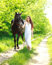 A girl in a long white dress with a horse goes on a country road background of green forest Royalty Free Stock Images