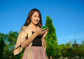 Girl look into mobilephone asia young and so funny on natural and blue sky background Stock Photography