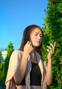 Girl look into mobilephone asia young on natural and blue sky background Royalty Free Stock Photos