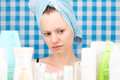 Girl is looking at cosmetic products in bathroom Royalty Free Stock Photo