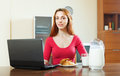 Girl looking e-mail in laptop during breakfast Stock Image