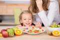 Girl looking at fruit salad in kitchen little cropped mother prepare the Royalty Free Stock Image