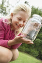 Girl looking at grasshopper in jar excited young outdoors Stock Images