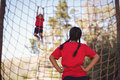 Girl looking at her friend while climbing net during obstacle course Royalty Free Stock Photo