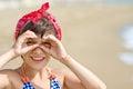 Girl looking through imaginary binocular on beach Royalty Free Stock Photo