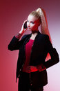 Girl looking like barbie doll beautiful blond in black suit and red topt holding mobile phone Stock Photography