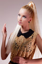 Girl looking like barbie doll portrait of beautiful blond in golden dress Royalty Free Stock Photo