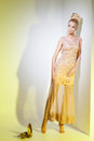 Girl looking like barbie doll portrait of beautiful blond in golden dress leaning on wall over yellow background Royalty Free Stock Photo