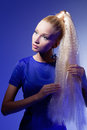 Girl looking like barbie doll portrait of beautiful blond in long blue dress over blue background Royalty Free Stock Photos