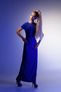 Girl looking like barbie doll portrait of beautiful blond in long blue dress over blue background Royalty Free Stock Images