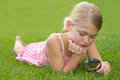 Girl looking through magnifying glass outdoors Stock Images