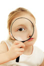 The girl looking through a magnifying glass sitting at table Royalty Free Stock Photography