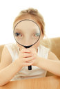 The girl looking through a magnifying glass sitting at table Stock Photography