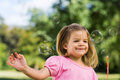 Girl looking at soap bubbles at park cute young the Royalty Free Stock Photography