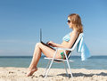 Girl looking at tablet pc on the beach summer holidays vacation technology and internet chair Stock Photos
