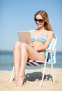 Girl looking at tablet pc on the beach summer holidays vacation technology and internet chair Stock Images