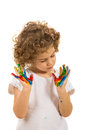 Girl looking to her messy hands in colorful paints isolated on white background Royalty Free Stock Photography
