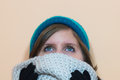 Girl looking upwards while she is wearing a fluffy scarf and a blue beanie Royalty Free Stock Photo