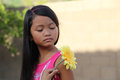Girl looking at yellow flower minority large Royalty Free Stock Photo