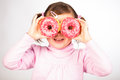 Girl looks through donuts Stock Photography