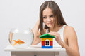 The girl looks at a goldfish and put her hand on the toy house Royalty Free Stock Photo