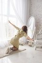 Girl looks at herself in the mirror cute light room knitted sweater winter morning Stock Photo