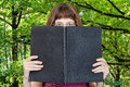 Girl looks over big book and green woods Royalty Free Stock Photo