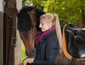 Girl looks to her horse is looking brown new forest pony Royalty Free Stock Image