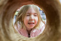 Girl looks through the tube closed eyes little caucasian and having fun Royalty Free Stock Images
