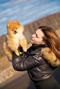 Girl looks up at the hands of puppy spitz beautiful happy owns a dog photographing outdoors Royalty Free Stock Images