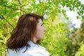 The girl looks upwards among green foliage Royalty Free Stock Photography