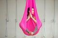 Girl lotus pose aerial antigravity yoga. Woman sits in hammock Royalty Free Stock Photo