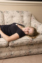 Girl lounging on couch blonde in her home wearing a black t shirt Royalty Free Stock Photos
