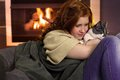Girl loving cat at home red hair teenager fondling sitting by fireplace Royalty Free Stock Photography