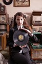 Girl with lp record in antique shop young suit holding old Stock Image
