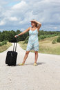Girl with luggage on the road Royalty Free Stock Photo
