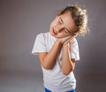 Girl lunatic hand under his cheek asleep standing on a gray background Royalty Free Stock Images