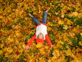 Girl lying in autumn leaves Stock Photos