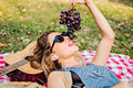 Girl lying and eating grapes in the park Royalty Free Stock Photo