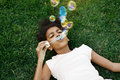 Girl lying on grass blowing bubbles Royalty Free Stock Photo