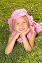 Girl lying on a grass little in polka dot dress and hat lies green lawn in summer park Royalty Free Stock Photo