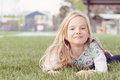 Girl lying in grass a little smiling as she lies the fresh spring Royalty Free Stock Images