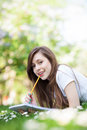 Girl lying on grass with workbook and pencil Royalty Free Stock Photos