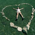 Girl lying on grass young in shorts and t shirt supine surrounded by stones formed into a heart shape Stock Photo