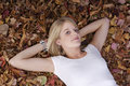 Girl lying on her back in autumn leaves Stock Photos