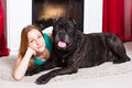 Girl lying near the fireplace with dog Cane Corso Royalty Free Stock Photo