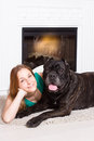 Girl lying near the fireplace with a dog Cane Corso Royalty Free Stock Photo